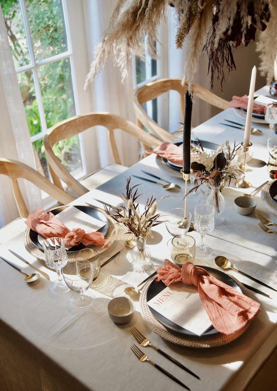 """<p>Use blush pink and navy blue for a modern take on a Thanksgiving table. The gold flatware adds a bit of festivity, while the dried florals bring a natural, laid-back touch. </p><p><a class=""""link rapid-noclick-resp"""" href=""""https://www.lifeslookingood.com/blog/rosh-hashanah-tablescape"""" rel=""""nofollow noopener"""" target=""""_blank"""" data-ylk=""""slk:See more at Life's Looking Good"""">See more at Life's Looking Good</a></p>"""