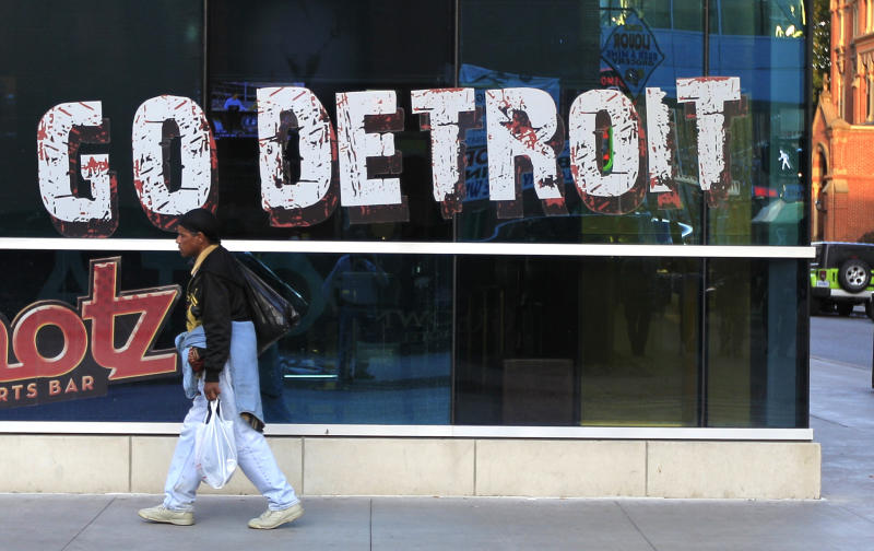 In this Oct. 24, 2012, photo, a pedestrian walks in Greektown in downtown Detroit. When baseball's World Series returns to Detroit this weekend for Game 3, television viewers will see vibrant crowds and skyline shots of the city. Yet beyond the hot dogs and home runs, Detroit is struggling to cross home plate. (AP Photo/Carlos Osorio)