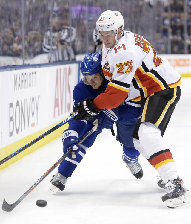 Calgary Flames centre Sean Monahan (23) ties up Toronto Maple Leafs left wing Zach Hyman (11) along the boards during the second period of an NHL hockey game Thursday, Jan. 16, 2020, in Toronto. (Nathan Denette/The Canadian Press via AP)