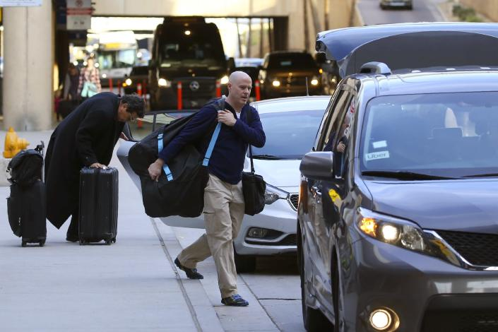FILE - In this Dec. 18, 2019, file photo, passengers find their rides at the Ride Share point as they exit Phoenix Sky Harbor International Airport in Phoenix. A dispute between ride-hailing companies and the city of Phoenix deepened on Monday, Feb. 10, 2020, as Arizona state lawmakers introduced legislation that would bar raising fees on Uber and Lyft at Sky Harbor airport. (AP Photo/Ross D. Franklin, File)