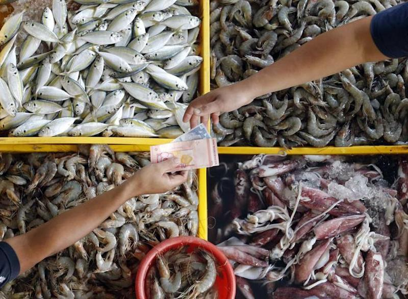 A fishmonger returns change to a customer at a market in Kuala Lumpur. — Reuters file pic