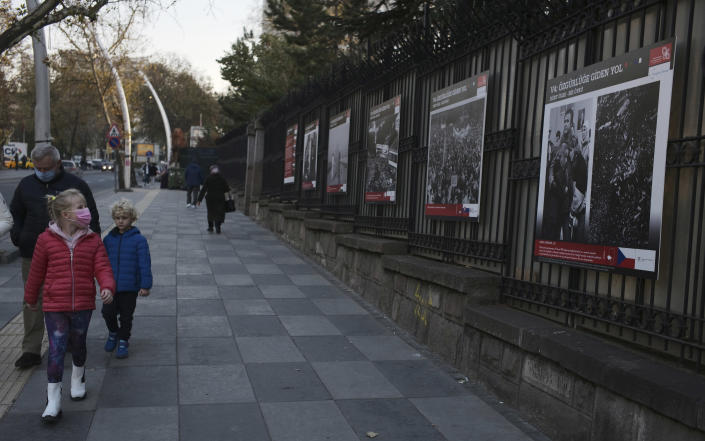 A teenager wearing a mask to help protect against the spread of coronavirus, looks at an open air photo exhibition, in Ankara, Turkey, Monday, Nov. 30, 2020.Turkey's President Recep Tayyip Erdogan has announced Monday the most widespread lockdown so far amid a surge in COVID-19 infections, extending curfews to weeknights and full lockdowns over weekends.(AP Photo/Burhan Ozbilici)