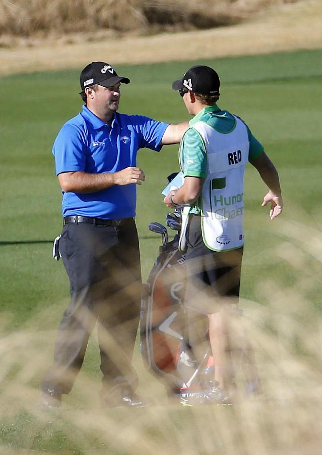 Patrick Reed, left, stretches with his caddie on the 12th fairway during the third round of the Humana Challenge PGA golf tournament on the Nicklaus Private course at PGA West, Saturday, Jan. 18, 2014, in La Quinta, Calif. (AP Photo/Matt York)