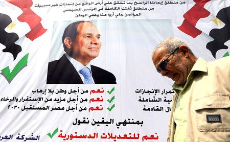 "FILE PHOTO: A man walks in front of a banner reading, ""Yes to the constitutional amendments, for a better future"", with a photo of the Egyptian President Abdel Fattah al-Sisi before the approaching referendum on constitutional amendments in Cairo, Egypt April 16, 2019. REUTERS/Mohamed Abd El Ghany/File Photo"