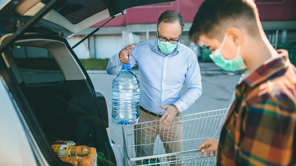 Father and son with surgical masks loading car trunk with groceries after shopping at parking loot during corona virus pandemic.