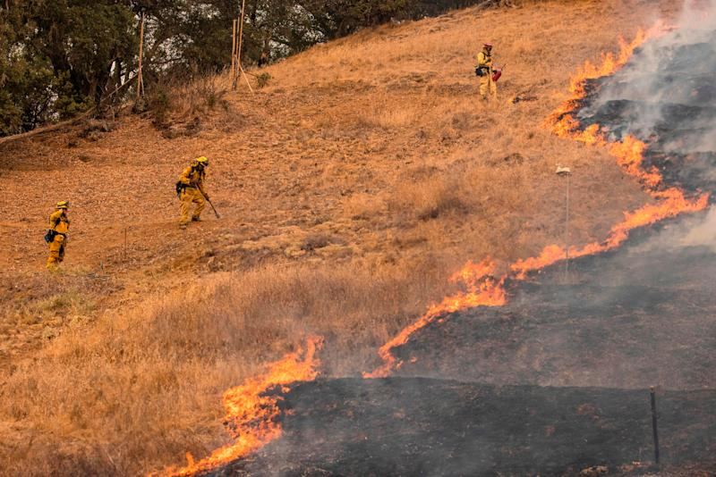 Firefighters scrape a fire line with hand tools as the Glass Fire burns in Napa Valley, Calif., on Sept. 29.