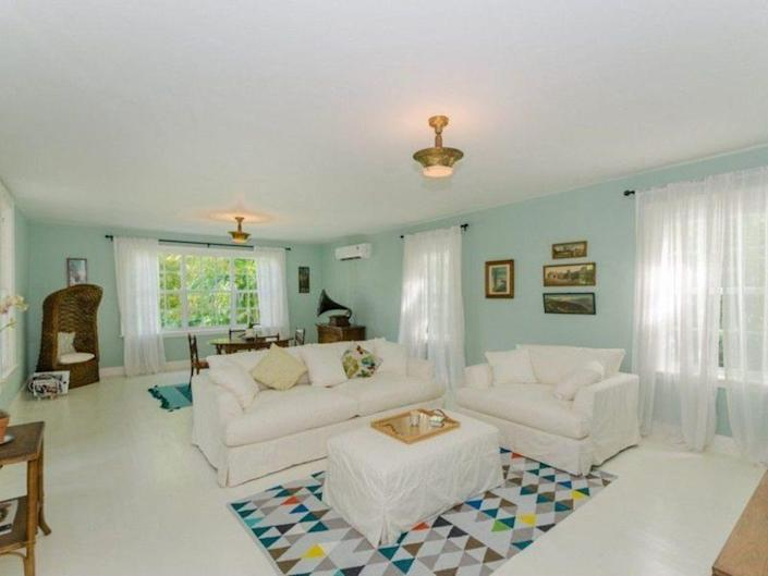 <p><i>Pictures of the home before its conversion show a springy pastel blue-green on the wall and a decidedly more colorful, homey room. <i>(Listing photo)</i><br></i></p>