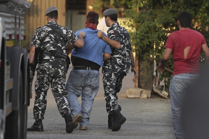 Policemen arrest a supporter of President Michel Aoun, center, who opened fire over the heads of protesters in the town of Jal el-Dib, north of Beirut, Lebanon, Wednesday, Nov. 13, 2019. It was the second shooting incident in as many days as tensions rise in Lebanon between supporters and opponents of President Michel Aoun amid nationwide protests. (AP Photo/Hassan Ammar)