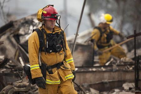 Firefighters search for victims in the rubble of a home burnt by the Valley Fire in Middletown, California, September 14, 2015. REUTERS/David Ryder
