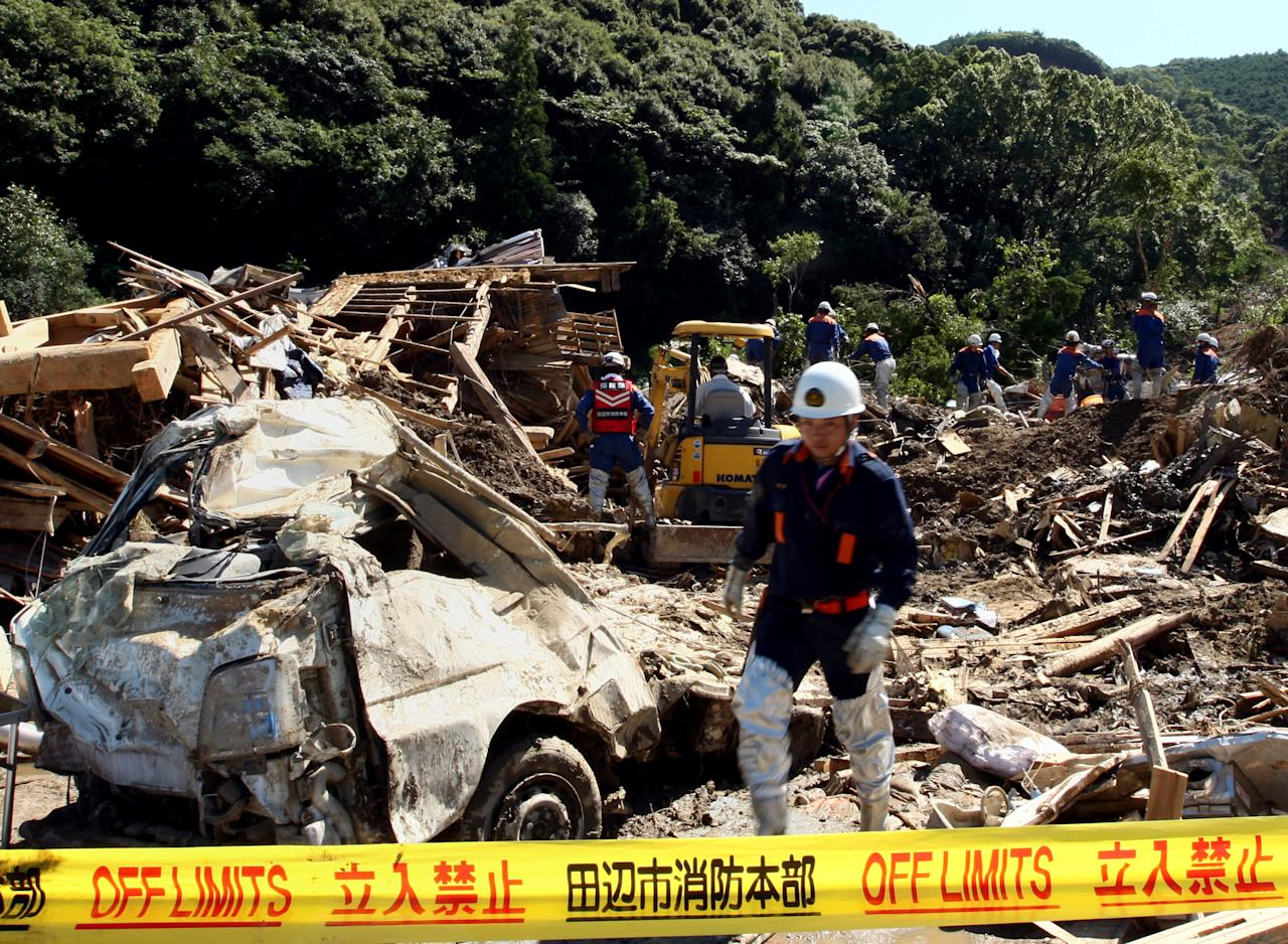TANABE, JAPAN - SEPTEMBER 06:  Members of Ground Self-Defense Force, firefighters and police officers continue the search for missing people among the debris of houses destroyed by a landslide caused by heavy rain delivered by Typhoon Talas on September 6, 2011 in Tanabe, Wakayama, Japan. Rescue teams and aid are being brought into the area in the aftermath of the tropical storm which hit western Japan over the weekend, leaving 42 people confirmed dead and over 50 people still missing.  (Photo by Buddhika Weerasinghe Getty Images)