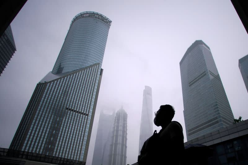 A man wearing a face mask walks in Lujiazui financial district in Pudong