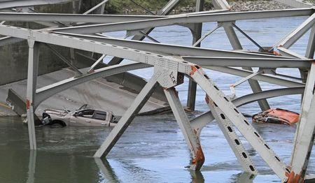 Cars are seen in the water as a span of highway bridge sits in the Skagit River