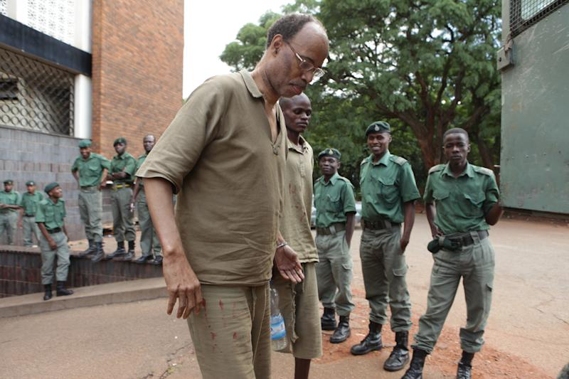 Former US Congressman Mel Reynolds, centre left, prepares to enter a prison truck while handcuffed following his court appearance at the magistrates courts in Harare, Thursday, February, 20, 2014. Reynolds was arrested in Zimbabwe for allegedly possessing pornographic material and violating immigration laws. (AP Photo/Tsvangirayi Mukwazhi)