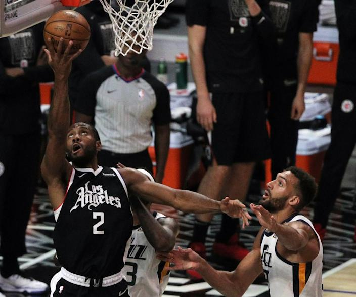 The Clippers' Kawhi Leonard scores on a reverse layup against the Jazz's Royce O'Neale, rear, and center Rudy Gobert, right.