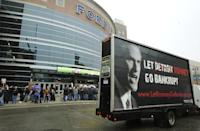 A rolling billboard truck drives around Ford Field in Detroit as protestors march where Republican presidential candidate Mitt Romney delivered a speech to the Detroit Economic Club, in Detroit Friday, Feb. 24, 2012. (AP Photo/The Detroit News, Daniel Mears) DETROIT FREE PRESS OUT