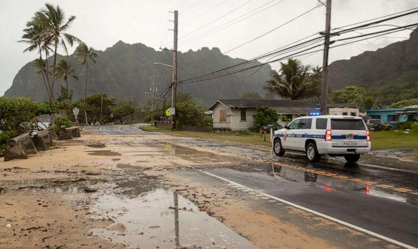 PHOTO: A police officer with the Honolulu Police Department inspects the sand and debris washed onto a closed portion of Kamehameha Highway, July 26, 2020, in Kaaawa, Hawaii. (Eugene Tanner/AP Photo)