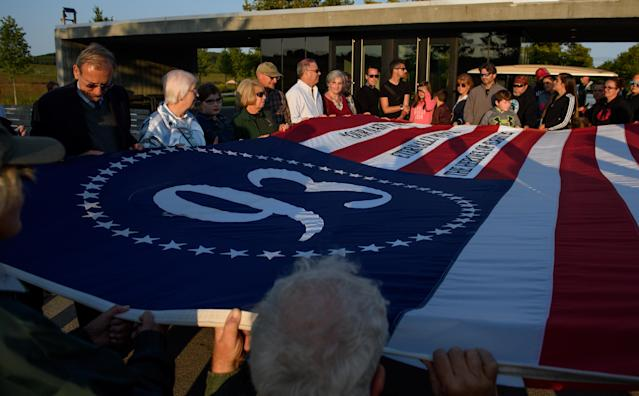 <p>Visitors unfurl a commemorative flag at the Flight 93 National Memorial on the 16th Anniversary ceremony of the Sept. 11 terrorist attacks, Sept. 10, 2017, in Shanksville, Pa. United Airlines Flight 93 crashed into a field outside Shanksville with 40 passengers and four hijackers aboard on Sept. 11, 2001. (Photo: Jeff Swensen/Getty Images) </p>