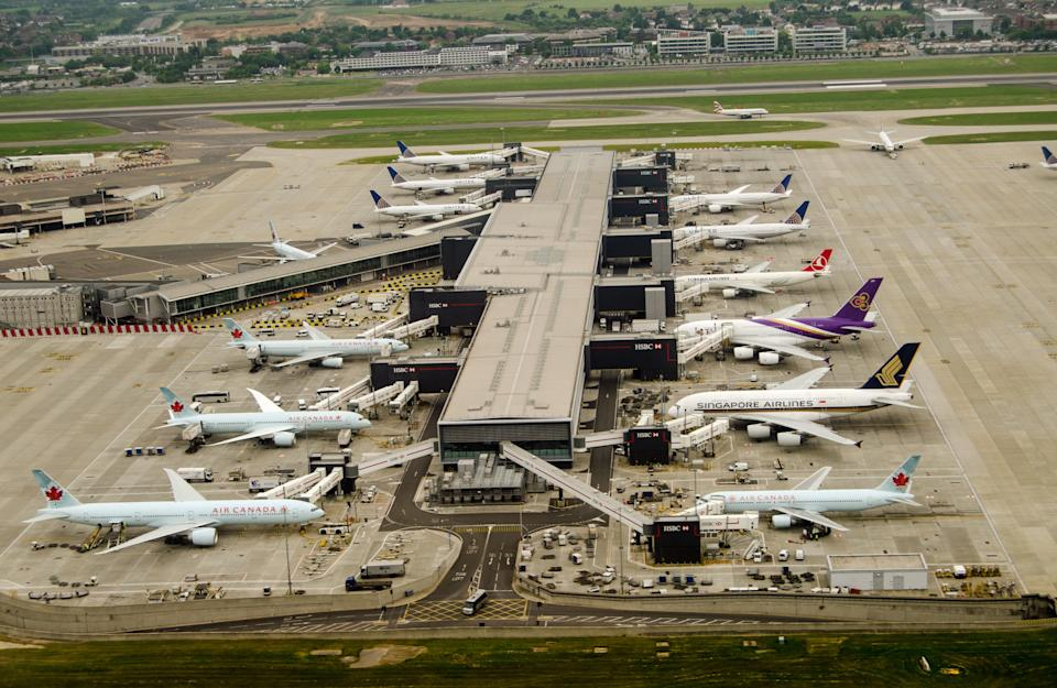 London, UK - May 30, 2016: Aerial view of aeroplanes standing at Terminal 2 of London Heathrow Airport on a cloudy day in May. Airlines using this terminal include Air Canada, Singapore Airlines and United Airlines.
