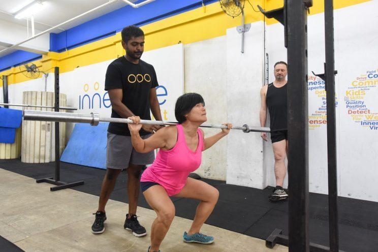 Wan Wai Yee, who is blind, performing squats under the supervision of coach Moses James. (PHOTO: Yahoo Newsroom)