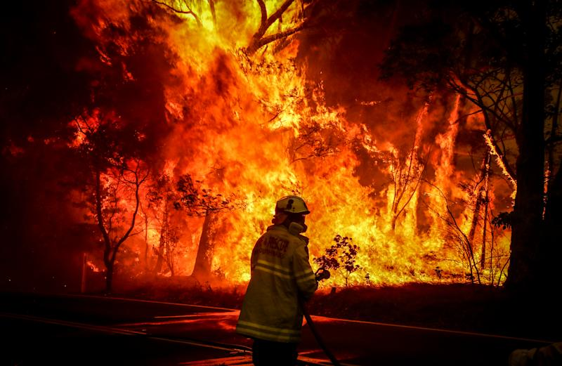 Fire and Rescue personnel prepare to use a hose in an effort to extinguish a bushfire as it burns near homes on the outskirts of the town of Bilpin.
