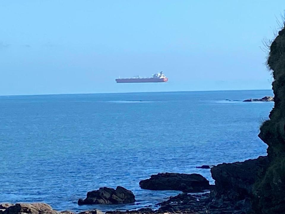 A tanker appears to float above the sea when viewed from the Cornwall coast (David Morris/APEX)