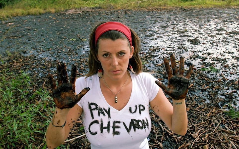 Zoe Tryon beside an open pit of crude oil near the town of Lago Agrio, Sucumbios, Ecuador - Clare Kendall /eyevine