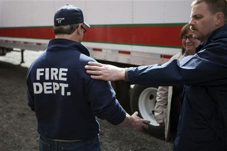 A friend (R) comforts Oso Fire Captain Seth Jefferds (L) who lost his wife and granddaughter in a massive mudslide, in Oso, Washington April 4, 2014. REUTERS/Max Whittaker