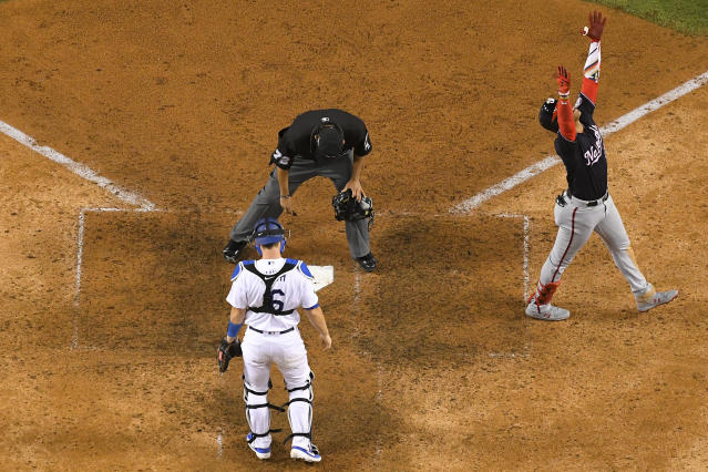 Washington Nationals' Juan Soto celebrates near Los Angeles Dodgers catcher Will Smith after scoring on his home run during the eighth inning in Game 5 of a baseball National League Division Series on Wednesday, Oct. 9, 2019, in Los Angeles. (AP Photo/Mark J. Terrill)