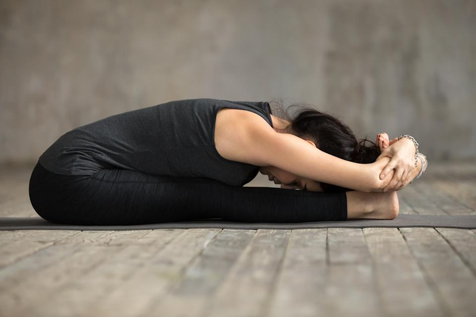Young yogi woman practicing yoga, doing paschimottanasana exercise, Seated forward bend pose, working out, wearing sportswear, black pants and top, indoor full length, gray wall in yoga studio