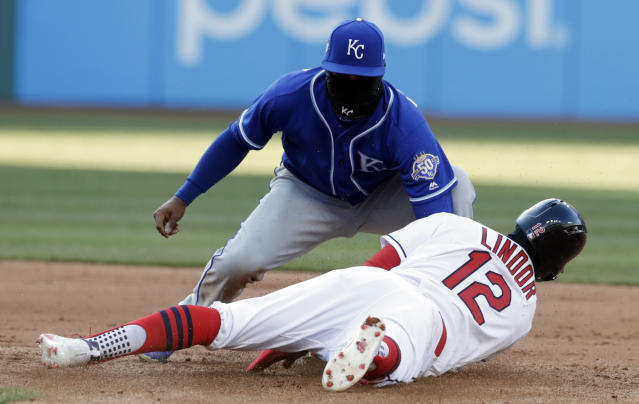 Kansas City Royals' Alcides Escobar tags out Cleveland Indians' Francisco Lindor on a steal in the eighth inning of a baseball game, Saturday, April 7, 2018, in Cleveland. (AP Photo/Tony Dejak)