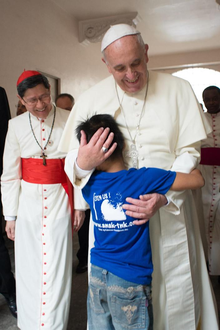 This handout picture released by the Vatican press office (Osservatore Romano) shows Pope Francis hugging a boy in Manila on January 16, 2015 (AFP Photo/Osservatore Romano)