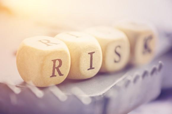 """The word """"risk"""" spelled out using dice."""