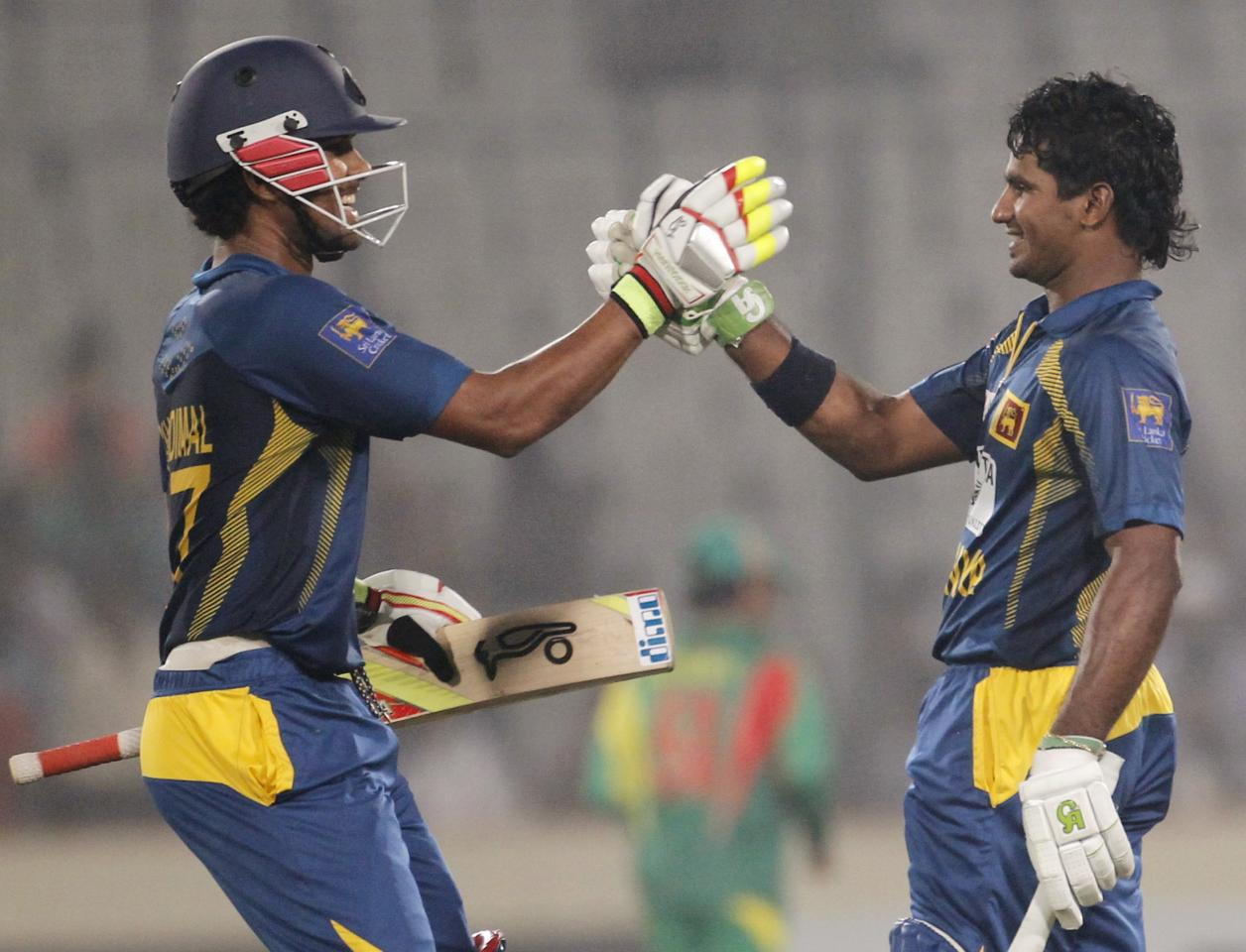 Sri Lanka's Dinesh Chandimal (L) congratulates team mate Kusal Perera after he scored a century against Bangladesh during their third one day international (ODI) cricket match of the series in Dhaka February 22, 2014. REUTERS/Andrew Biraj (BANGLADESH - Tags: SPORT CRICKET)