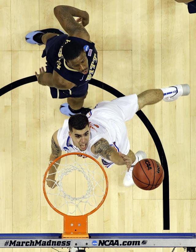 Florida guard Scottie Wilbekin, bottom, gets past Pittsburgh forward Lamar Patterson for a shot during the second half in a third-round game in the NCAA college basketball tournament in Orlando, Fla., Saturday, March 22, 2014. Florida won 61-45.(AP Photo/John Raoux)