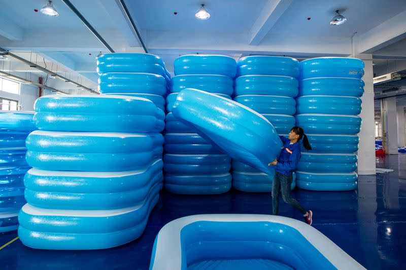 A worker piles up newly made inflatable swimming pools at a workshop of a company manufacturing sports equipment in Haian, Jiangsu