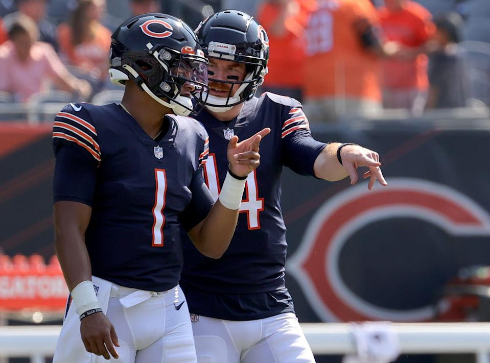 Quarterback Justin Fields #1 talks with Quarterback Andy Dalton #14 of the Chicago Bears talks before the game against the Cincinnati Bengals at Soldier Field on September 19, 2021 in Chicago, Illinois.