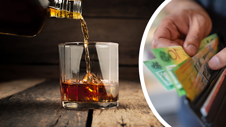 Whiskey being poured from a bottle into a glass over ice and a man removing $100 notes from a wallet.