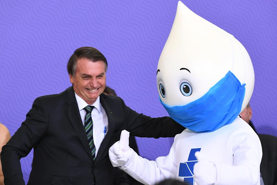 Brazilian President Jair Bolsobaro poses with Ze Gotinha, symbol of Brazilian vaccination campaigns during the launch of the  national vaccination plan against the novel coronavirus Covid-19 at Planalto Palace in Brasilia, on December 16, 2020. - The government has not released a date for the start of the vaccination but commits to start the process 5 days after the approval of a vaccine by the health agency (ANVISA) and expects to take 12 to 16 months to vaccinate the entire Brazilian population. (Photo by EVARISTO SA / AFP) (Photo by EVARISTO SA/AFP via Getty Images)