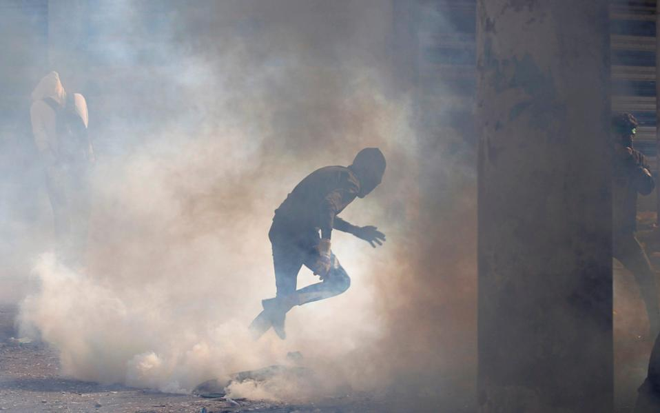 A demonstrator runs away from tear gas during anti-government protests in Baghdad on November 24, 2019 - REUTERS