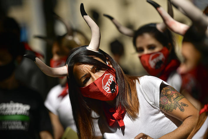 Demonstrators wear faces masks protection while protesting against San Fermin's bullfighting in front of the bull ring due canceled this year by the conoravirus, in Pamplona, northern Spain, Tuesday, July 7, 2020. (AP Photo/Alvaro Barrientos)
