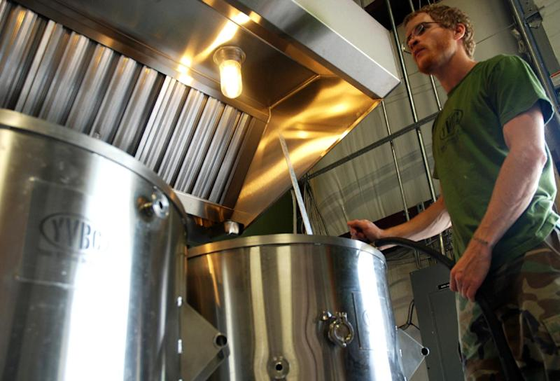 """In a Wednesday, Aug. 14, 2013, photo, Neil McCanon, Iraq War veteran and head brewer at Young Veterans Brewing Co., adds water to the brew kettle as he prepares to brew """"Pineapple Grenade Hefeweizen,"""" at the Virginia Beach, Va., brewery. The brewery set to open in September in military-heavy Hampton Roads is part of a growing number of craft breweries popping up throughout Virginia and the country. Virginia, which is celebrating its second craft beer month in August, has seen the industry grow from about 40 craft breweries last year to more than 60 in 2013, with countless more in the works. (AP Photo/Michael Felberbaum)"""