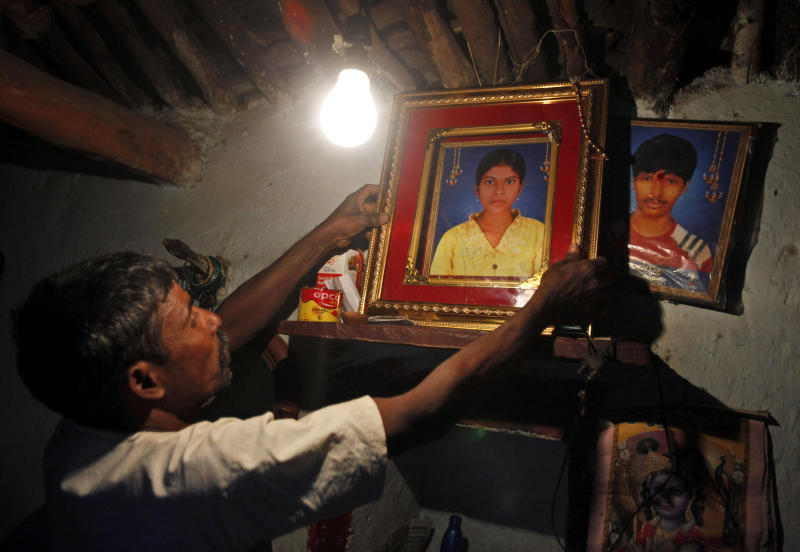 """In this photo taken Tuesday, Feb. 7, 2012, Petla Narasimhulu holds a portrait of his 18-year-old daughter Petla Lalitha at their home in Godhumaguda village of Vikarabad district, about 70 kilometers (43 miles) from Hyderabad, India. Lalitha, pressured until she handed over her last 150 rupees ($3), meant for a school examination fee, drank pesticide while leaving a suicide note reading: """"Work hard and earn money. Do not take loans."""" A wave of suicides among the impoverished residents of India's Andhra Pradesh state was blamed on the relentless tactics of agents from microfinance companies, which give small loans intended to lift up the very poor. (AP Photo/Mahesh Kumar A.)"""