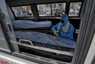 FILE PHOTO: A man wearing a protective suit sits next to the bodies of the victims of the coronavirus disease (COVID-19) inside an ambulance at a mortuary of a COVID-19 hospital in Ahmedabad
