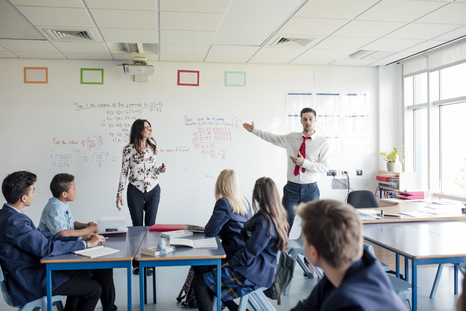 Rear view of students in a classroom while getting taught.