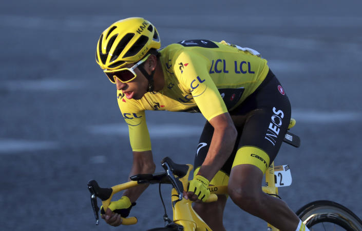 FILE - In this July 28, 2019, file photo, Colombia's Egan Bernal wearing the overall leader's yellow jersey, rides on the Champs-Elysees in Paris during the 21st stage of the Tour de France cycling race. It has been 35 years since a French cyclist rode down Paris' Champs-Elysees in the 21st and final stage on way to winning the grueling three-week Tour de France. Julian Alaphilippe won two stages and wore the yellow jersey as the overall Tour leader for 14 days last year. But Bernal became the first Latin American winner of the race, and at 22 the youngest post-World War II winner of the Tour. The final stage was supposed to be Sunday, but will now be Sept. 20 after the Tour was pushed back. (AP Photo/Thibault Camus, File)