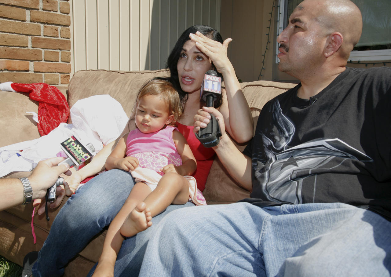 """""""Octomom"""" Nadya Suleman, left, holds 20-month-old daughter Nariah Solomon while radio personality David """"Tattoo"""" Gonzalez holds a mic as they talk to media about Suleman's yard sale and auction to raise money at her home in La Habra, Calif. on Saturday, Sept. 25, 2010. Gonzalez was helping promote the event. (AP Photo/Jason Redmond)"""