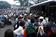 People queue to try to find a spot on a bus to travel to the city of San Antonio near the Colombian border at the bus station in San Cristobal, Venezuela December 14, 2017. REUTERS/Carlos Eduardo Ramirez