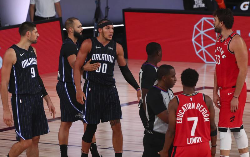Orlando Magic forward Aaron Gordon (00) is held back by guard Evan Fournier (10) after getting fouled by Toronto Raptors guard Kyle Lowry (7) in the second half of an NBA basketball game Wednesday, Aug. 5, 2020, in Lake Buena Vista, Fla. (Kim Klement/Pool Photo via AP)