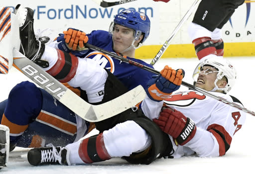 New York Islanders defenseman Sebastian Aho (28) takes down New Jersey Devils left wing Miles Wood (44) during the second period of an NHL hockey game Saturday, Feb. 24, 2018, in Newark, N.J. (AP Photo/Bill Kostroun)