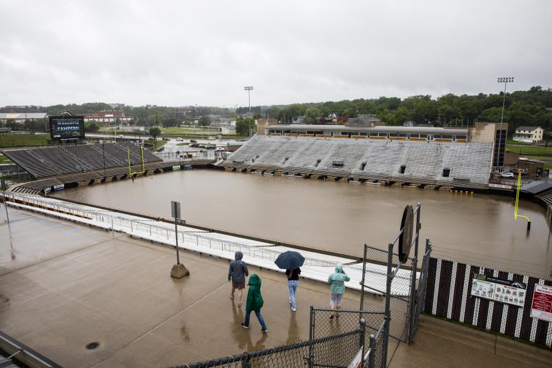 People look at the flooded Waldo Stadium on the campus of Western Michigan University in Kalamazoo, Mich., Thursday, June 20, 2019. (Photo: Joel Bissell/Kalamazoo Gazette via AP)